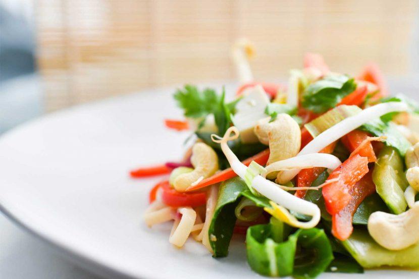 Plant-based tofu vegetable pad thai on white plate