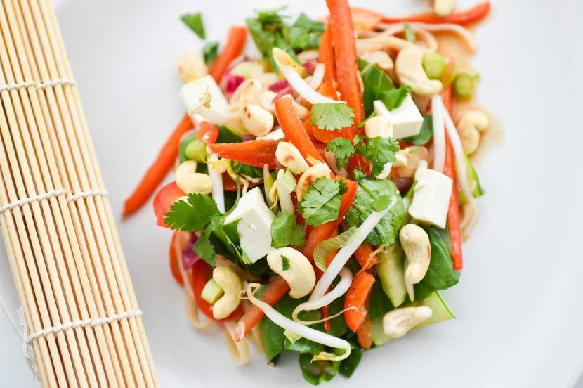 Plant-based tofu vegetable pad thai on white plate with lime