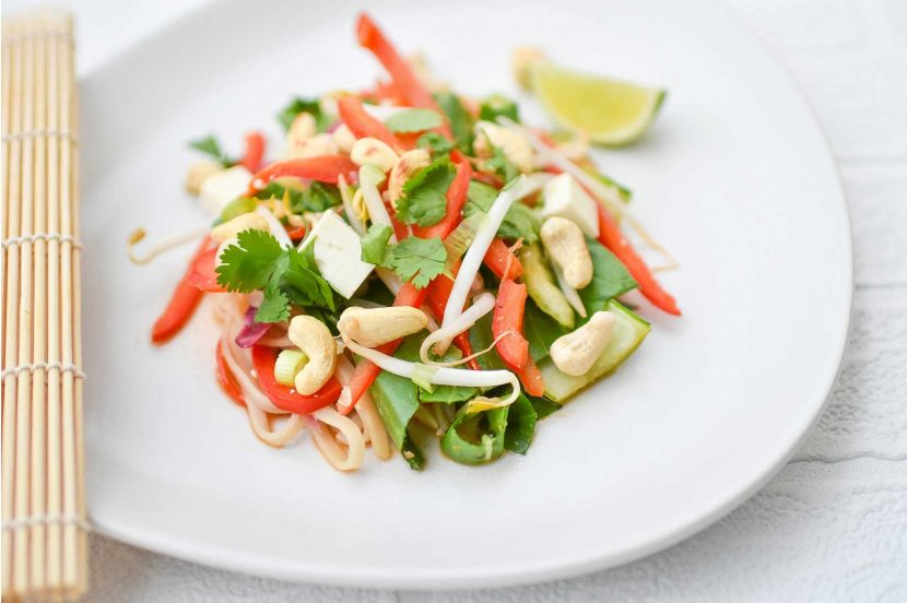 Plant-based tofu vegetable pad thai on white plate with lime wedge