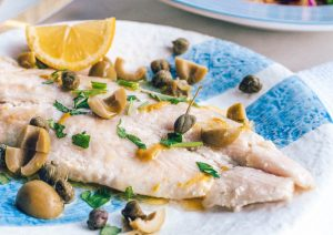Mediterranean lentils with Sea Bass on blue and white plate served with capers olives and lemon