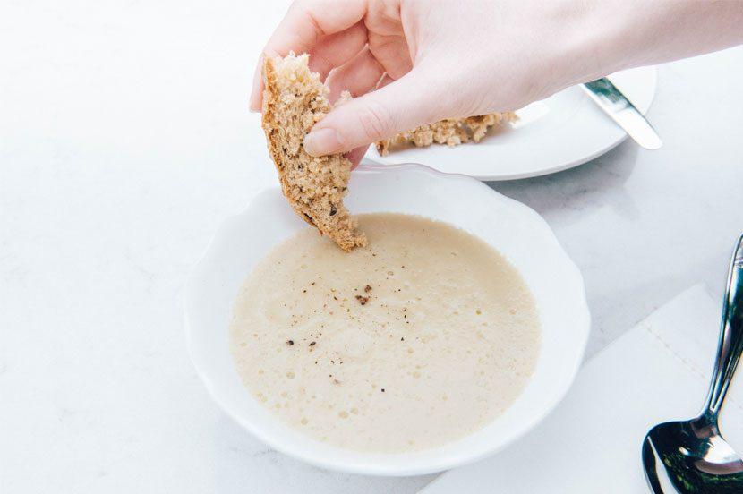 Jerusalem artichoke Soup in white bowl with gluten free bread