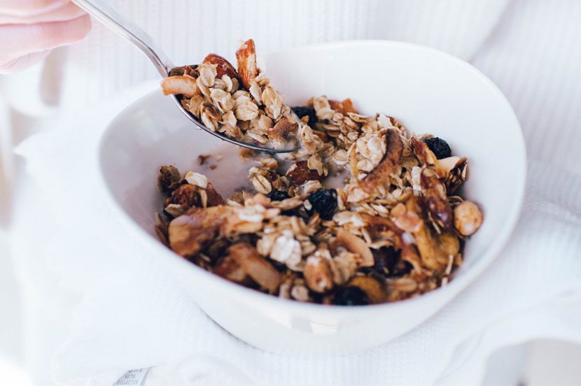 Cherry, banana & coconut flake granola with white towel and cotton