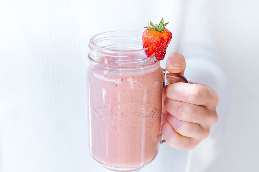 Strawberry and banana smoothie held in girl's hands