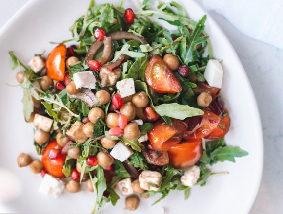 Chickpea, avocado, rocket, tomato, pomegranate, feta and mint salad with balsamic dressing on white plate