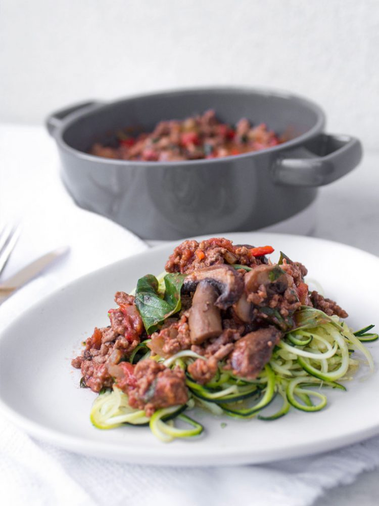 Spiralized Courgetti Bolognese with mushrooms, onion, chilli and basil on white plate