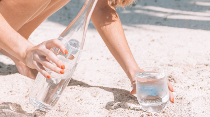Girl drinking bottled water on beach in Mauritius